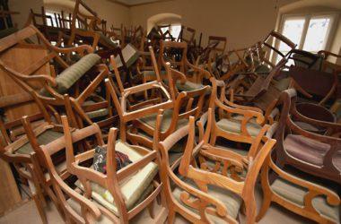 Stos starych, drewnianych, tapicerowanych krzeseł w pomieszczeniu Pałacu w Rybnej.