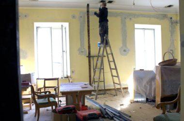 Mężczyzna na drabinie w roboczym stroju w pokoju w trakcie remontu.