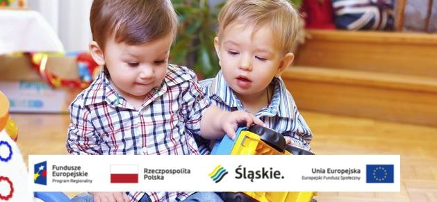Dwóch chłopców bawi się autkiem.