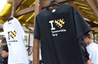 Czarna i biała koszulka z logo I love Tarnowskie Góry na wieszaku