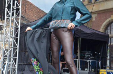 Na scenie kobieta w skórzanych leginsach i jakli, ściąga fartuch.