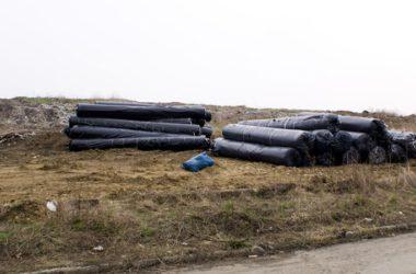 Rulony czarnej folii na ziemi przy wysypisku śmieci.