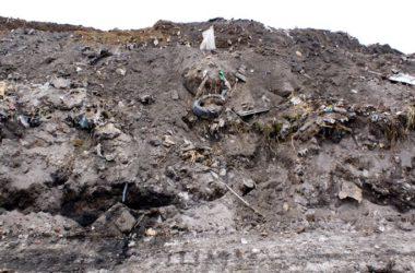 Góra śmieci wmieszanych w glebę.