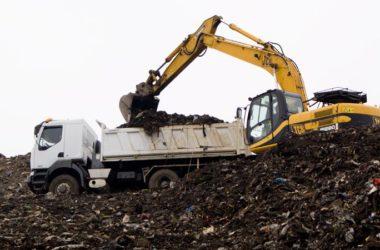 Koparka z ciężarówką na górze śmieci.