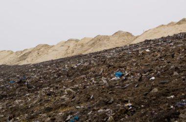 Śmieci zmieszane z glebą na tle kopców z piaskiem.