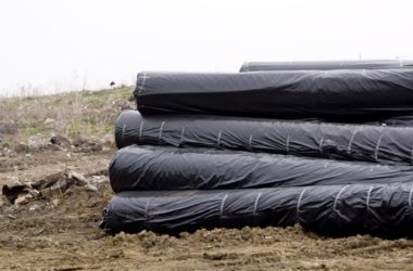 5 rulonów czarnej folii leży na ziemi.