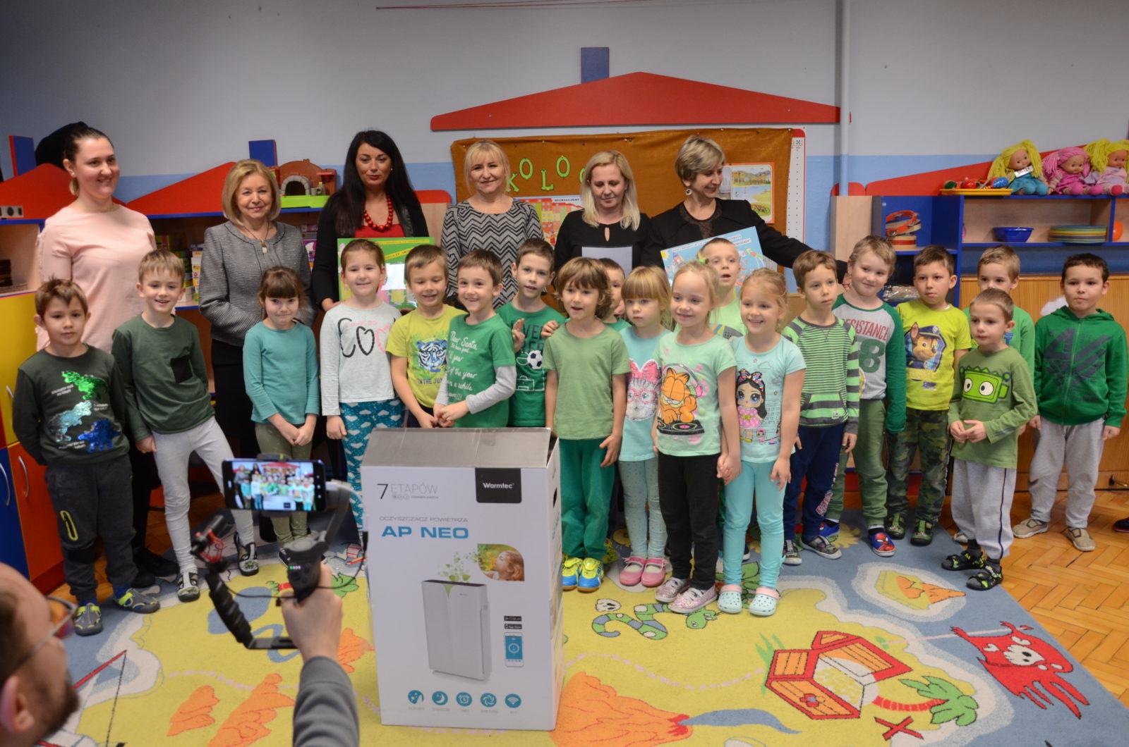 Dzieci stoją w przedszkolu. Pozują do wspólnego zdjęcia. Na pierwszym planie leży opakowanie oczyszczcza powietrza.