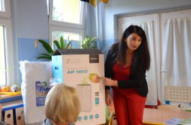 Kobieta wskazuje na kartonowe opakowanie z oczyszczacza powietrza. Opowiada o urządzeniu.