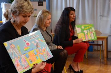 Trzy kobiety siedzą na krzesełkach. Trzymają w rękach obrazki stworzone przez dzieci.