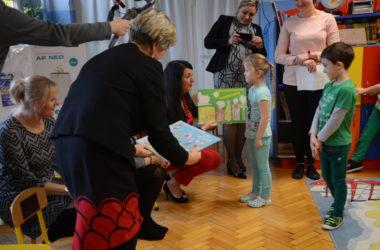 Dzieci wręczają obrazki przedstawicielkom władz.