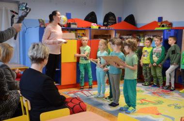 Dzieci stoją w rzędach. Prezentują swoje obrazki.