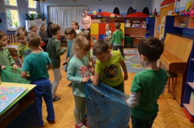 Dzieci bawią się w przedszkolu. Uczą się segregować śmieci. Na pierwszym planie dwójka dzieci stoi z workiem na papier. Chłopczyk wrzuca do worka karton.