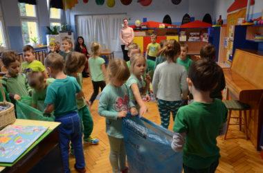 Dzieci bawią się w przedszkolu. Uczą się segregować śmieci. Na pierwszym planie chłopiec i dziewczynka trzymają worek na papierowe odpadki.