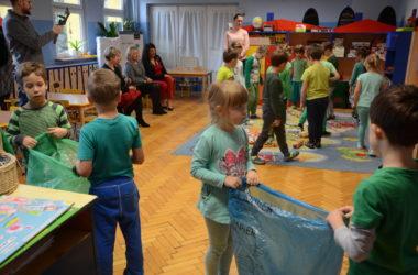 Dzieci bawią się w przedszkolu. Uczą się segregować śmieci. Na pierwszym planie dzieci trzymają worki na papier i szkło.