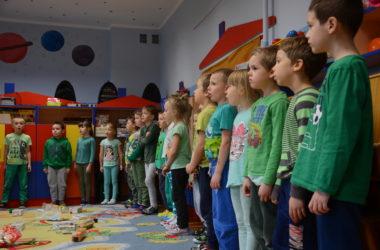 Grupa dzieci jest w przedszkolu. Stoją w szregu i śpiewają. Przed nimi, na dywanie leżą porozrzucane śmieci.