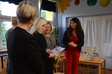 Cztery uśmiechnięte kobiety rozmawiają ze sobą. Jedna z kobiet trzyma dyplom dla dzieci.