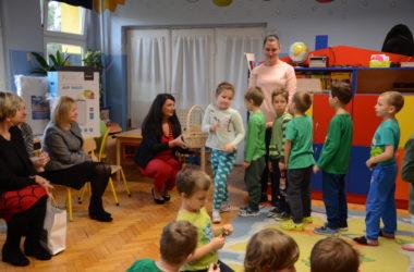 Dzieci stoją w kolejce po cukierki. Kobieta trzyma koszyk z cukierkami..