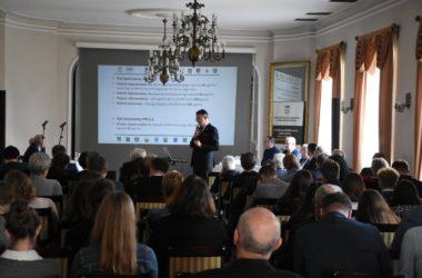 Mężczyzna przemawia, Na pierwszym planie siedzą uczestnicy konferencji na temat ekoloii. W tle widać przedstawicieli władz Tarnowskich Gór.