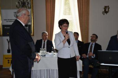 Mężczyzna i kobieta przemawiają przez mikrofony. W tle widać przedstawicieli władz Tarnowskich Gór.