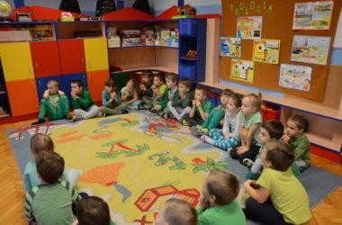 Dzieci siedzą w kółku na dywanie. Słuchają wykładu o ekologii.