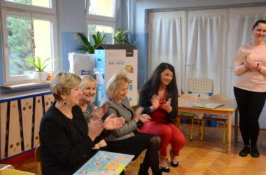 Cztery kobiety siedzą na krzesełkach. Jedna kobieta stoi. Uśmiechają się i klaszczą.