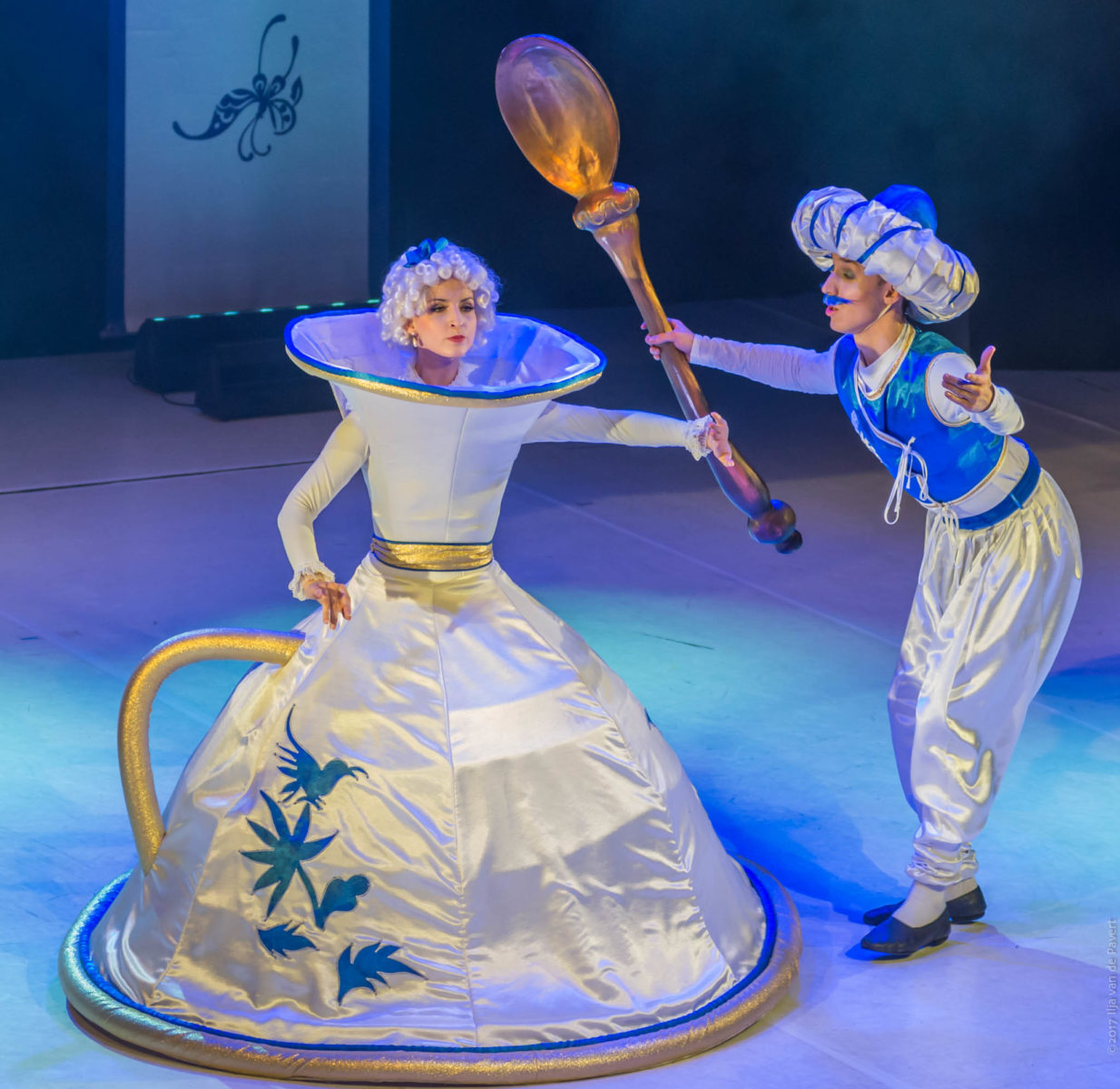 Dwóch tancerzy, aktorów jest na scenie w kostiumach. Kobieta jest przebrana w kostium filiżanki. Mężczyzna nosi arabski strój, na głowie ma turban, a w ręku ogromną łyżeczkę..