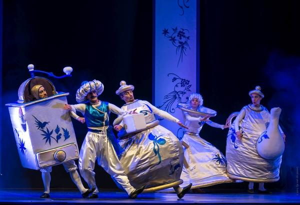Aktorzy tańczą na scenie w kostiumach młynka do kawy, cukiernicy, filiżanki, dzbanka.
