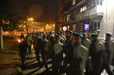 Przemarsz delegacji wojska przez ulice Tarnowskich Gór w nocy.