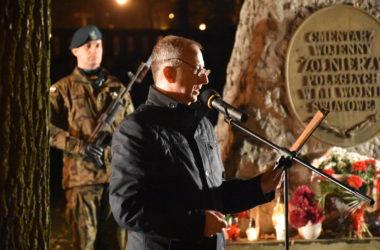 Mężczyzna wygłasza przemówienie do mikrofonu. W tle, obok pomnika stoi żołnierz. Pod pomnikiem leżą kwiaty oraz zapalone znicze.