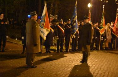 Dwóch mężczyzn w mundurach stoi na przeciwko siebie. W tle przedstawiciele organizacji stoją w rzędzie i trzymają flagi.