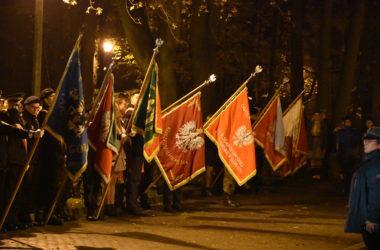 Przedstawiciele władz i organizacji pochylają swoje flagi.