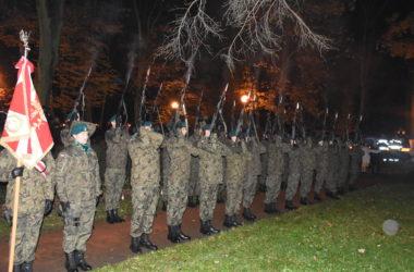 Żołnierze stoją w dwóch rzędach. Prezentują broń. Pierwszy żołnierz trzyma flagę.
