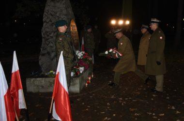 Przedstawiciele wojskowi składają kwiaty pod pomnikiem. Przy pomniku stoi dwóch żołnierzy. Na pierwszym planie stoją ustawione flagi Polski.