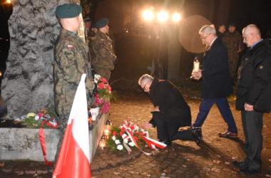 Burmistrz Arkadiusz Czech składa kwiaty pod pomnikiem. Przy pomniku stoi dwóch żołnierzy.