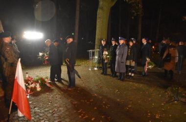 Przedstawiciele władz stoją w rzędzie by złożyć kwiaty pod pomnikiem.