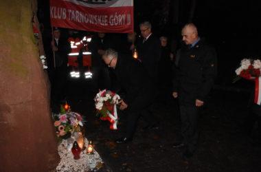 Burmistrz miasta składa kwiaty pod pomnikiem. W tle stoją osoby trzymające baner z napisem