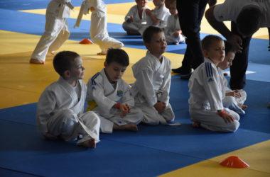 Czterej chłopcy siedzą w judogach na macie. W tle inni zmali zawodnicy się pojedynkują.