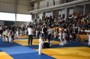 Wnętrze Hali Sportowej. Młodzi zawodnicy siędzą na macie. Kibice są na trybunach.