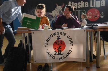 Organizatorzy wydarzenia siedzą przy stole. Rozmawiają ze sobą. W tle widać bawiącą się dziewczynkę.