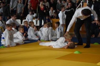 Grupa zawodników siedzi na macie. Na pierwszym planie dwaj chłopcy walczą z sobą.