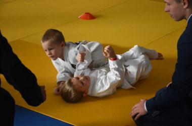 Dwóch chłopców walczy ze sobą na żółtej macie. Dwóch sędziów w garniturach przygląda się walce.