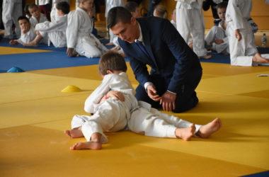 Dwóch chłopców walczy ze sobą na żółtej macie. Sędzia klęczy przy chłopcach, monitoruje pojedynek.