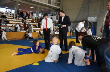 Dwóch chłopców walczy ze sobą w niebieskich judokach. Sędziowie monitorują walkę. Inni chłopcy przyglądają się walce.