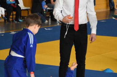 Chłopcy walczą w judokach. Jeden leży na macie, drugi stoi nad nim. Chłopców pilnuje sędzia z czasomierzem.
