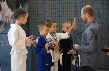 Organizator przyznaje nagrody czterem chłopcom za udział w turnieju. Przybija jednemmu z nich piątkę.