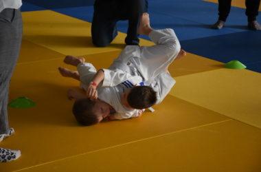 Dwóch chłopców walczy ze sobą na żółtej macie. Są ubrani w judoki.