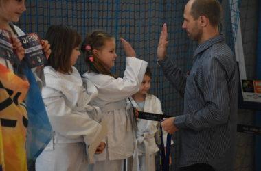 Pięć dziewczynek odbiera nagrody. Organizator przybija piątkę jednej z nich.