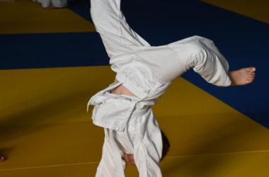 Chłopiec ubrany w judokę staje na rękach. W tle dzieci siedzą na macie.