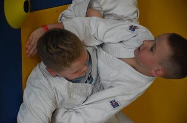 Dwóch chłopców pojedynkuje się na żółto-niebieskiej macie.