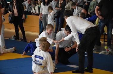 Trzech chłopców w judokach siedzi na macie przy dwóch sędziach. Czwarty chłopiec przybija piątkę z sędzią. Wszyscy oglądają listę. W tle trybuny z widzami.